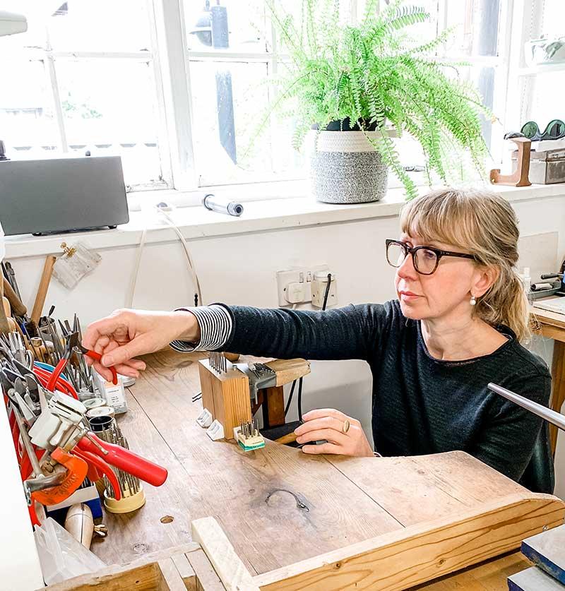 Jacks Turner at her comtemporary jewellery workbench, in her bristol workshop.